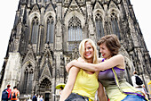 Two young women in front of the Cologne Cathedral, Cologne, North Rhine-Westphalia, Germany
