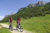 Couple mountainbiking, Kampenwand, Chiemgau range, Chiemgau, Bavaria, Germany