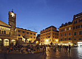 People sitting on steps of a fountain, Santa Maria in Trastevere church in background, Rome, Italy