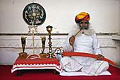 Senior man sitting at a veranda of a museum, Meherangarh Museum, Jodhpur, Rajasthan, India.