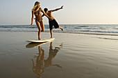 Adult, Adults, Bathing suit, Bathing suits, Beach, Beaches, Bikini, Bikinis, Blonde, Blondes, Board, Boards, Boy, Boys, Caucasian, Caucasians, Coast, Coastal, Color, Colour, Contemporary, Daytime, Evening, Exterior, Fair-haired, Female, Full-body, Full-le
