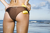 Adult, Adults, Back view, Beach, Beaches, Bikini, Bikinis, Body care, Bottle, Bottles, Bottom, Buttock, Buttocks, Color, Colour, Contemporary, Daytime, Detail, Details, Exterior, Female, Figure, Hands on the waist, Holiday, Holidays, Human, Leisure, One,