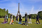 People doing Yoga, Eiffel Tower. Paris. France