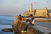 El Malecon on the background the Castillo de los Tres Reyes del Morro. La Havana. Cuba