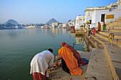 Pilgrims bathing in the Pushkar Holy lake during the Pushkar camel fair. Pushkar. Rajasthan. India. Asia