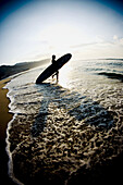 Silhouette of a surfer entering the water at sunrise