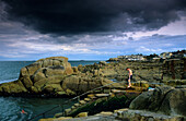People bathing in the sea under dark clouds, Sandy Cove, County Dublin, Ireland, Europe
