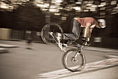 A teenager on his trial bike during a stunt in the evening, Wagram, Austria