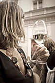 Blond woman holding a wine glass turning away, Linz, Upper Austria, Austria