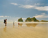 Mother with children hiking through shallow water, Wharariki Beach, northwest coast, South Island, New Zealand