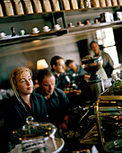 Young woman operates old italian espresso machine E61 at Mojo Café, Wellington, North Island, New Zealand