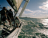 Three men on a sailing boat at full speed, Waitemata Harbour on the horizon, Auckland, North Island, New Zealand