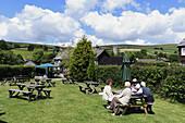 Guests sitting in garden of the Rugglestone Inn, Widecombe-in-the-Moor, Dartmoor National Park, Devon, England, United Kingdom