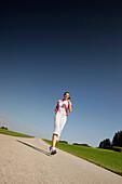Woman walking along road, Munsing, Bavaria, Germany