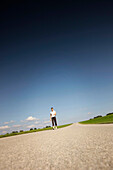 Jogger standing on road, Munsing, Bavaria, Germany