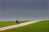 Couple jogging along road, Munsing, Bavaria, Germany