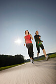 Two women running along road, Strasslach-Dingharting, Bavaria, Germany