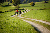 Four people running along dirt road, Munsing, Bavaria, Germany