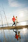 Couple jogging along lake Starnberg, Ambach, Bavaria, Germany