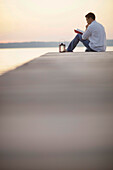 Man sitting on jetty while reading a book, Ambach, Lake Starnberg, Bavaria, Germany