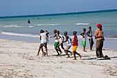 Kenyan boys playing football at the Public Beach of Mombasa, Kenya, Africa