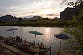 People relaxing on jetties at the river Nam Xong at sunset, Vang Vieng, Vientiane Province, Laos