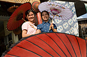 Two young burmese women with umbrellas made of paper and bamboo in Mandalay, Myanmar, Burma