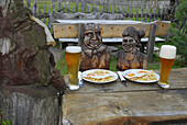 Carved couple at a table with food and wheat beer, alpine lodge Sulzenau, Stubaier Alps, Stubai, Tyrol, Austria