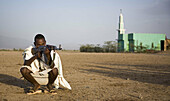Afar man holding gun and mosque in background. Ethiopia. African tribes
