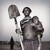 Dasanech woman and child holding shovel. South Ethiopia, African tribes
