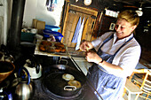 Woman baking fritters, doughnuts, at the Freudenreich lodge on the Brecherspitz, Schliersee, Bavaria, Germany