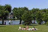 Young people sunbathing at Lake Constance, Konstanz, Baden-Wurttemberg, Germany