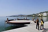 People sitting along the promenade at Lake Geneva, Montreux, Canton of Vaud, Switzerland