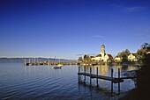 Kirche und Schloss am Seeufer unter blauem Himmel, Wasserburg, Bodensee, Bayern, Deutschland
