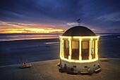 Illuminated beach pavilion at dusk, Borkum island, East Friesland, North Sea, Lower Saxony, Germany