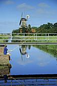 Child fishing at a canal, windmill in background, Rhauderfehn, Lower Saxony, Germany