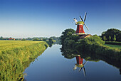 Windmill reflecting in a canal at Greetsiel, East Friesland, Lower Saxony, Germany