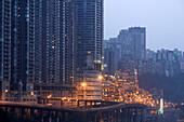 Dark, futuristic looking skyscrapers and the high illuminated Hongyadong Folklor Mall, Chongqing, China, Asia