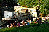 Young people sitting along the banks of a canal, Berlin, Germany