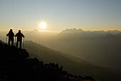 Two Hikers on Glanderspitze looking at Krahberg and Lechtaler Alpen range, Venet, Oetztaler Alpen range, Tyrol, Austria