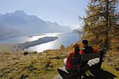 Couple sitting on bench above lake Sils, Piz da la Margna in background, Upper Engadin, Engadin, Grisons, Switzerland