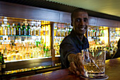 Smiling barkeeper serving a glass of whiskey, Bascule Bar, Cape Grace Hotel, Cape Town, South Africa, Africa