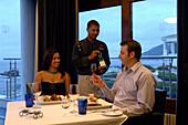 Ein Paar sitzt an einem Tisch, ein Kellner serviert Wein, Restaurant Azur, The Twelve Apostles Hotel, Kapstadt, Südafrika, Afrika