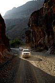 Two all-terrain vehicles on a road in the mountains, Al Hajar mountains, Wadi Bani Auf, Oman, Asia