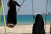 Two local girls on a swing at the beach, Al Fujairah, United Arab Emirates