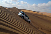 An all-terrain vehicle driving down a sand dune, Wahiba Sands, Oman, Asia