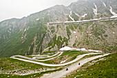 Tunnel in Berglandschaft, Drei Motorradfahrer, Bergstraße, St. Gotthard, Schweiz