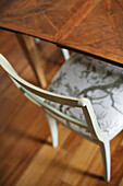 Antiques white chair and table on a parquet floor