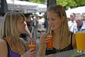 Two young women drinking freshly juice, Viktualienmarkt, Munich, Bavaria, Germany
