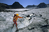 Woman crossing stream on Pers glacier, Piz Trovat and Piz Cambrena in background, Upper Engadin, Engadin, Grisons, Switzerland